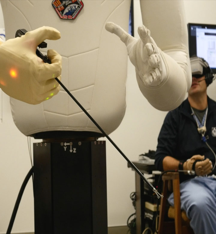 R2 holding a surgical tool during a teleoperated medical procedure test session with the Methodist Hospital surgeons and NASA engineers.